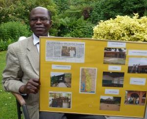 Antoine Bankoley mit Fotos und Zeitungsbeiträgen über seine soziale Arbeit in Togo. Foto (c): Helmut Burlager