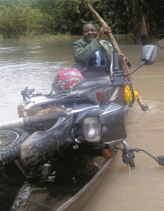 Moses Lambon. Wenn er einen Fluss überquert, um zu seinen Klienten zu gelangen, nimmt er sein Motorrad mit. Foto: OID